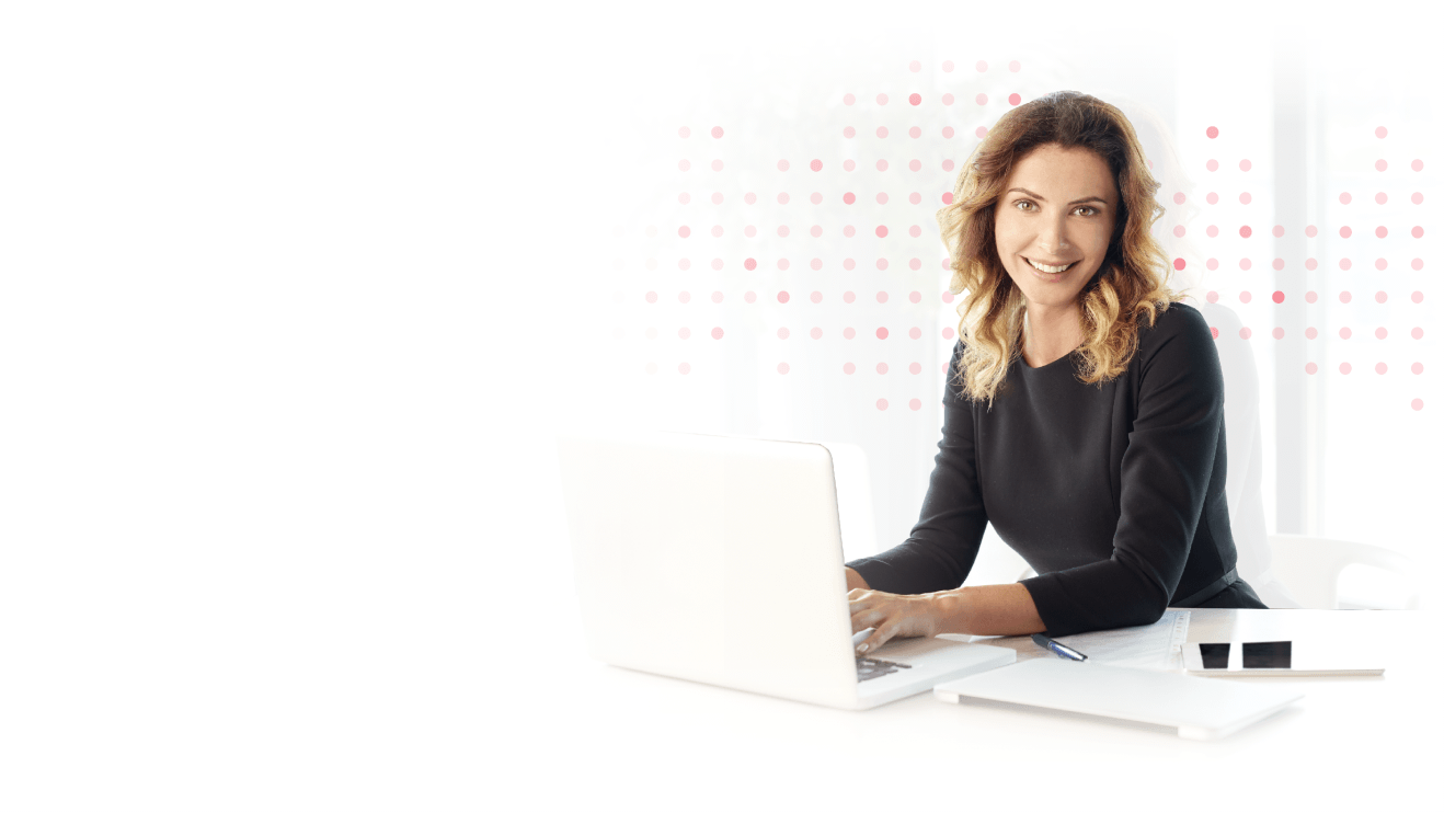 Female marketer smiling in front of laptop.